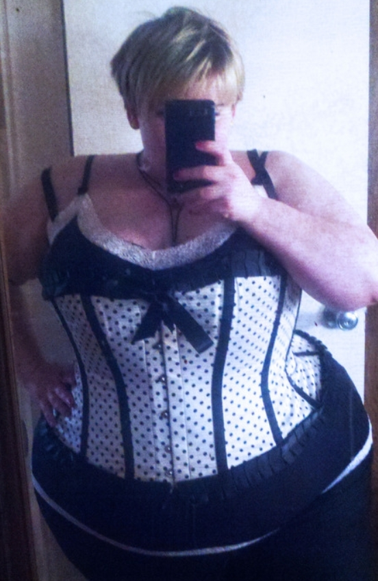 A thighs-up photo of Sugar, wearing a white corset with black trim and polka-dots, and taking the photo with their phone, which hides their face.