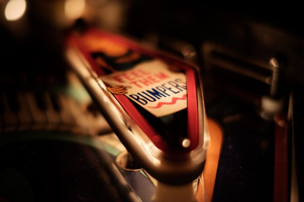 "A macro photo of a bumper slingshot on a pinball machine - the bumper is chrome with a red band and a sign that reads, ""Feel them bumpers,"" with ""bumpers"" underlined. The sign appears to be held by a character with a beard, but the rest of the character is out of the light and focus."