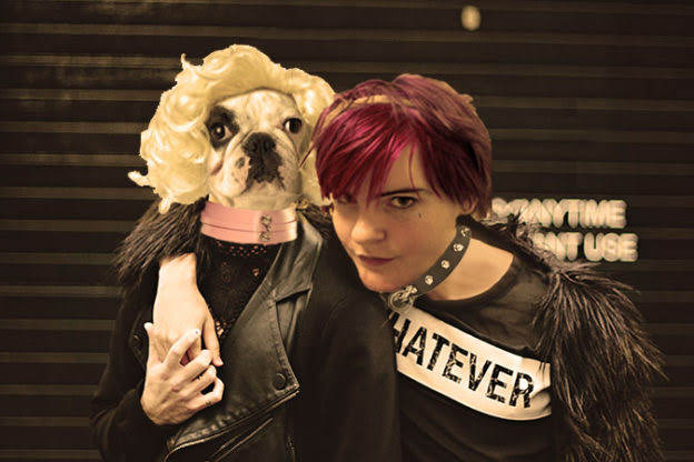 A photoshopped picture of two people in black outfits standing together with arms around one another. The person on the viewer's left has a bulldog's head photoshopped onto their neck, and a blonde wig on the bulldog. The person on the right has Sugarcunt's head photoshopped onto it.
