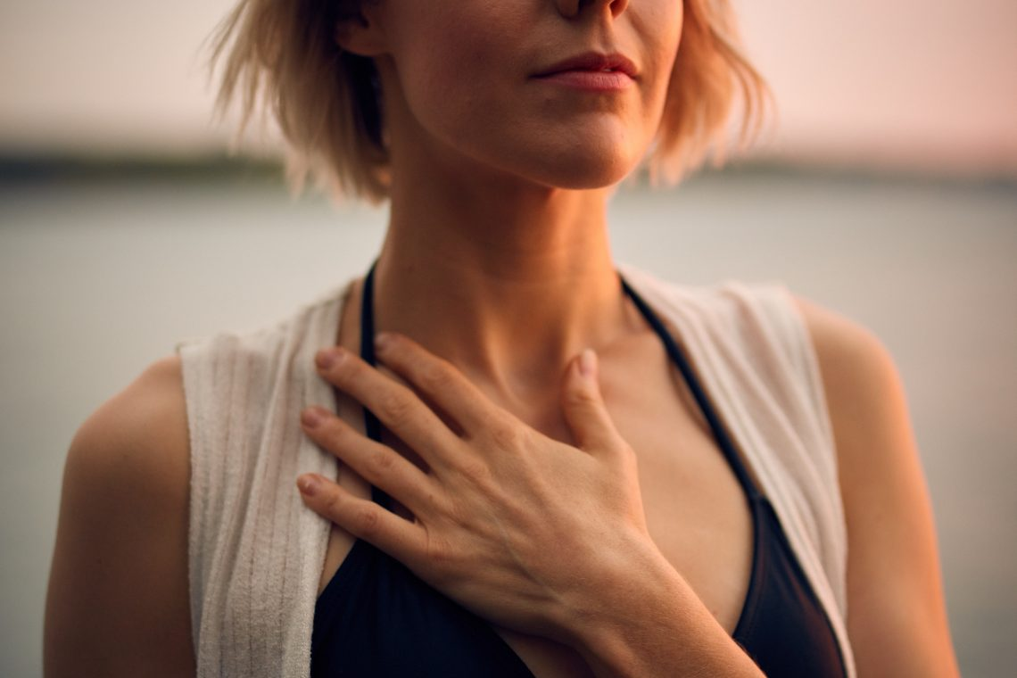 Photo of a white person with a gentle short bob hair cut holding their hand over their chest. Their eyes are closed and the sun is setting behind them. THey wear a white vest and black top, their hand covering their heart.
