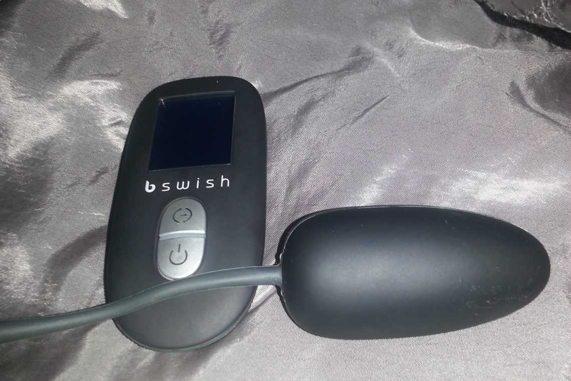 Photo of the Bnaughty Unleashed, a black egg vibrator with a wireless tail hanging off the back, and its black battery-operated remote on silver sheets