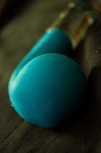The Jopen Key Comet G-Spot Wand on a black sheet. The blue Key is sky blue with a glass handle, and is curved with a slightly bulbous tip to hit the G-spot. The photo is taken from eye-level with the bulb.