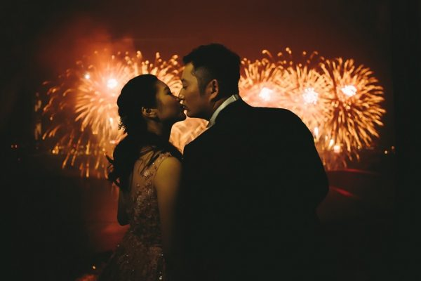 Photo by Jeremy Wong on Unsplash of an Asian couple standing in front of orange fireworks in the night, shoulder to shoulder and leaning together to kiss gently on the lips.