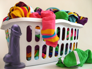 Photo composite with a Tantus T-Rex photoshopped in front of a laundry basket overflowing with colorful clothes and socks,.