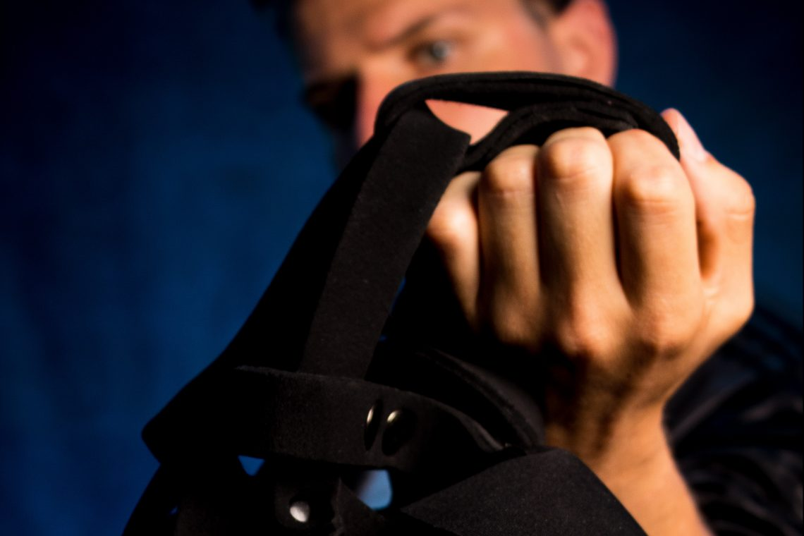 Photo of an AMAB person holding up a black harness in front of a blue background. Their face is largely obscured by the fist and harness, and their tightly-balled fist on the harness is the focus of the photo.