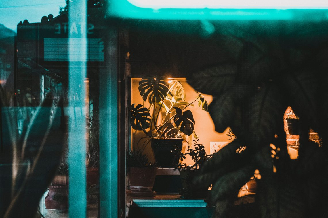 """Photo of the window of a tattoo parlor, a green neon sign drawing the eye, though only half is visible - it's the first half of the word """"Tattoo"""""""